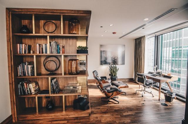Izba zariadený dreveným nábytkom, drevená podlaha a veľké sklenené dvere.jpg