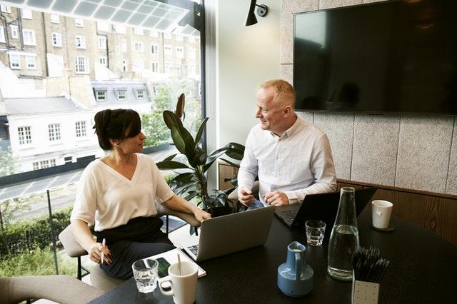 Muž a žena sedia pri stole v kancelárií a diskutujú.jpg