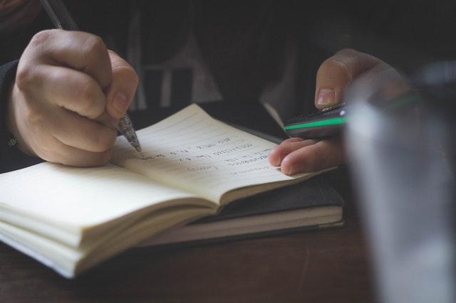Chlapec pozerá do mobilu a píše si poznámky